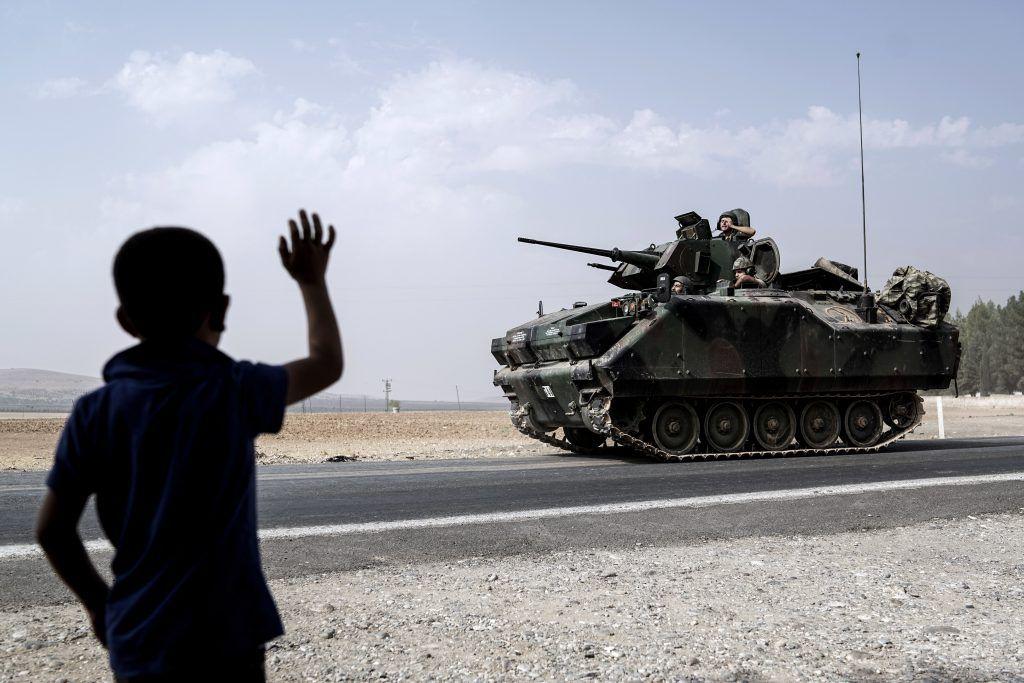 Un niño saluda a tropas turcas que viajan hacia la frontera siria en Karkamis, Turquía, el viernes 26 de agosto de 2016. Foto de AP.