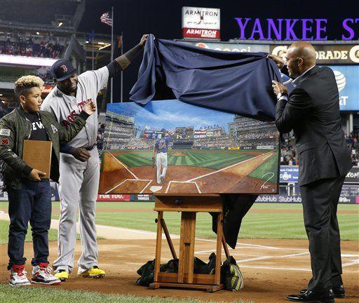 El bateador designado David Ortiz (segundo a la izquierda) y su hijo D'Angelo (izquierda) observan cuando el retirado pitcher Mariano Rivera devela una pintura que los Yanquis de Nueva York el obsequiaron a Ortiz el jueves 29 de septiembre de 2016. (AP Foto/Kathy Willens)