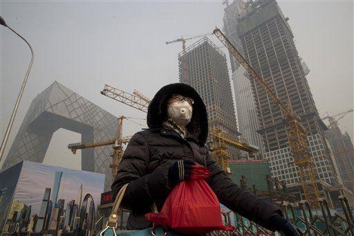 Una mujer que viste una mascarilla facial pasa por delante de una obra bajo la persistente smog que cubre Beijing, el 6 de enero de 2017. Las autoridades de la capital china crearon una nueva policía medioambiental, la útima iniciativa para luchar contra la niebla contaminante en el país. (AP Foto/Ng Han Guan)