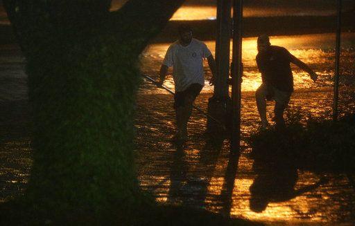 David Amerson y T.J. Krueger caminan por una calle anegada por el paso del huracán Nate en Mobile Alabama